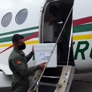 Um policial militar do Batalhão de Aviação da Brigada Militar carregando uma caixa de isopor para dentro do avião